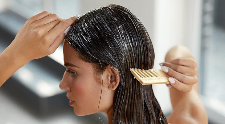 femme appliquant un traitement lissant sur ses cheveux